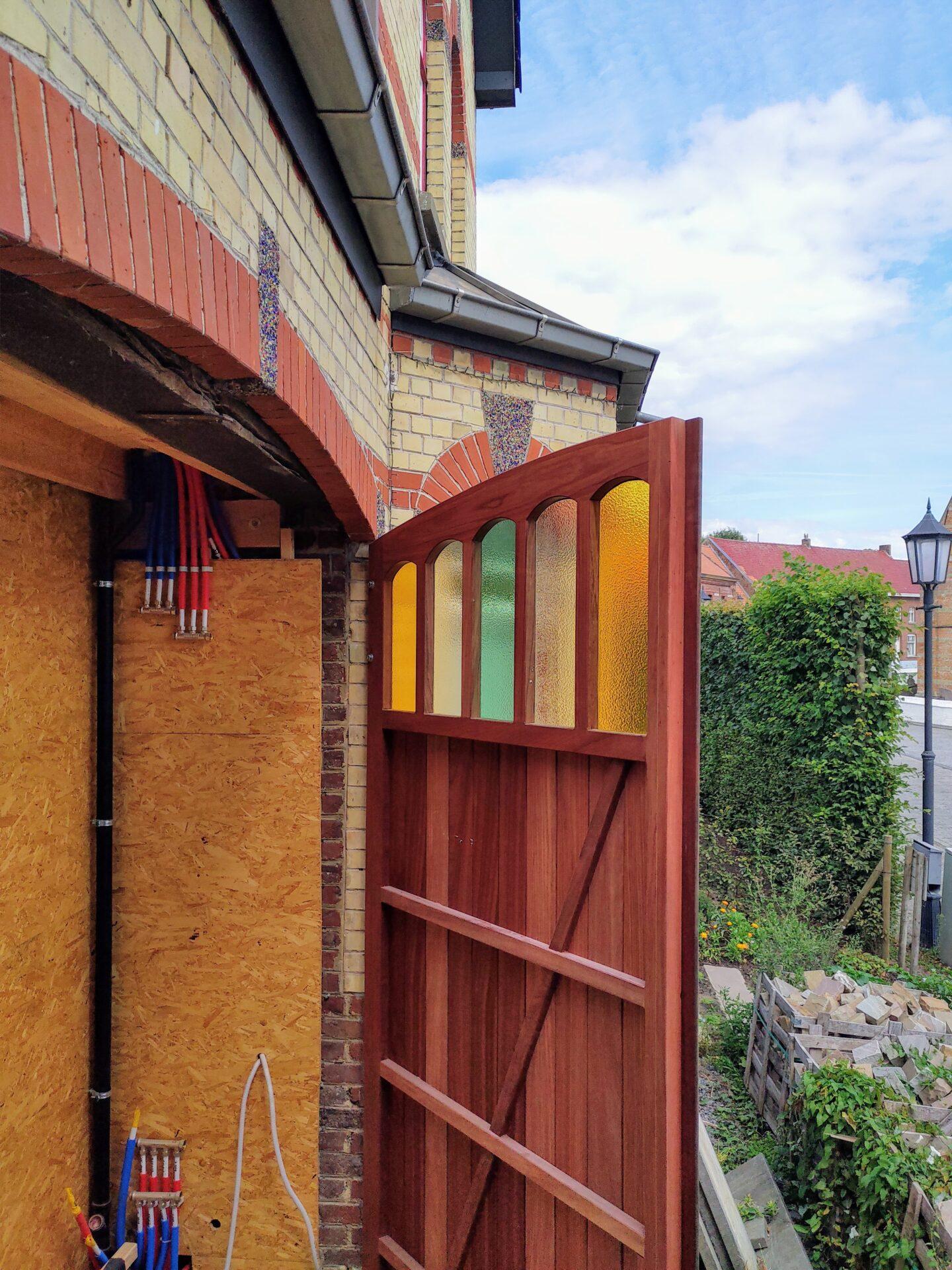 Plaatsing gekleurd glas in poort Rozebeke